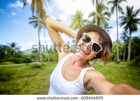 young beautiful hipster woman making selfie in tropical rainforest, hat, sunglasses, stylish, summer vacation in thailand, happy, fun, enjoying, ray of sunshine, sunny