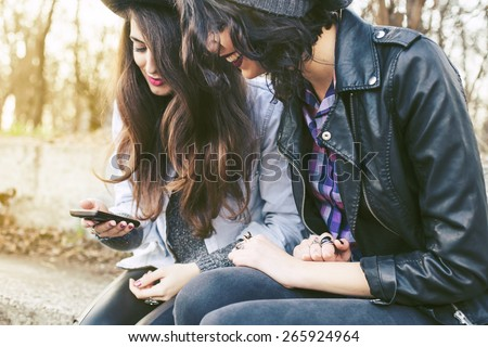 Young beautiful hipster women using smart phone in the city - stock photo