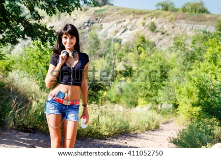 young beautiful hispanic girl walking on mountain road, listen to music, holding a bottle of water. summer sunny day. copy space. - stock photo