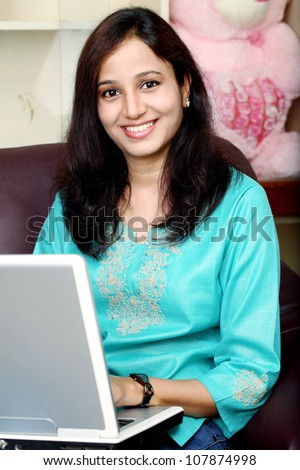 Young beautiful Indian woman using laptop at home - stock photo
