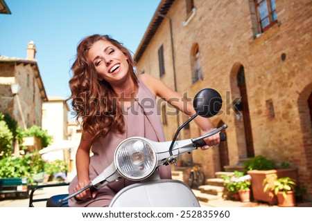Young beautiful italian woman sitting on a italian scooter. - stock photo