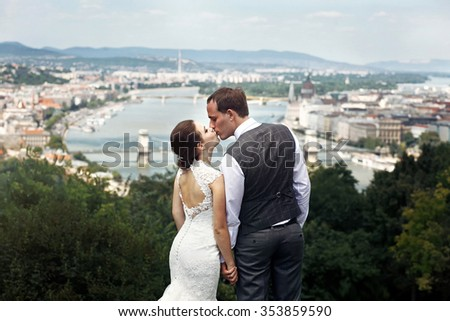 Young beautiful kissing couple of newlyweds a romantic walk in the park in Budapest, Hungary