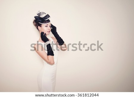 Young beautiful lady dressed in a proper outfit for horse racing with hat and gloves, fashion on the field, vintage matte effect - stock photo