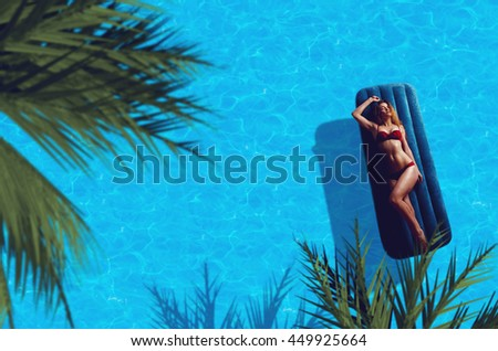 young beautiful lady in red bikini lying on the sun by the pool and sunbathing - stock photo