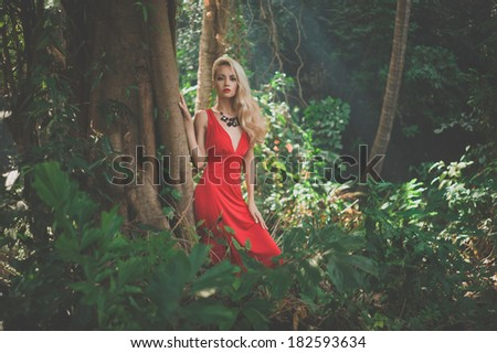 Young beautiful lady in red dress in tropical forest - stock photo