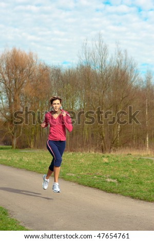 Young beautiful lady jogging in a park.