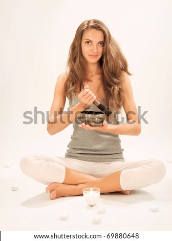 Young beautiful lady relaxing with nepal singing bowl and candle