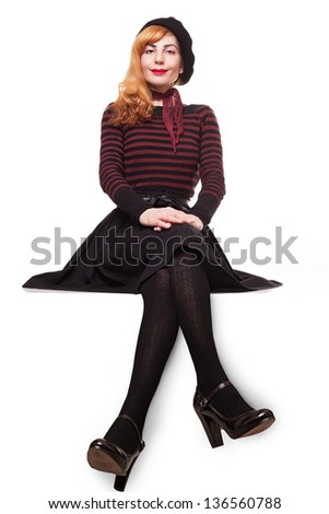young beautiful lady sitting on an edge of a platform, smiling and looking at you isolated on white background - stock photo