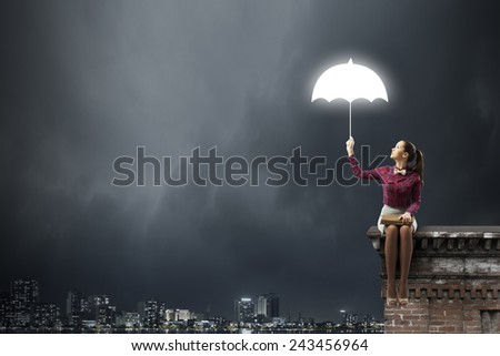 Young beautiful lady sitting on building roof and reading book