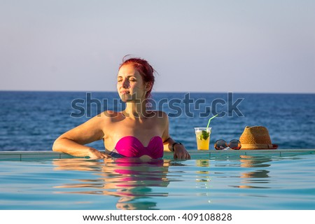 Young Beautiful Lady Standing in Swimming Pool with Cocktail, Glasses, Hat and looking at the Sea, Crete - stock photo