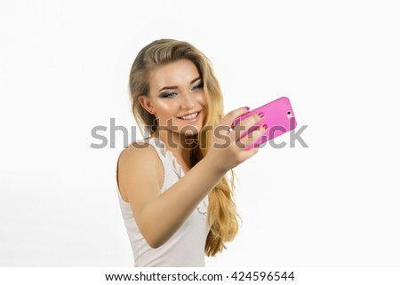 Young beautiful lady taking a selfie self portrait of herself smiling at he camera.Pretty hipster girl taking selfie. Close up portrait of a attractive woman holding a smartphone digital camera. - stock photo