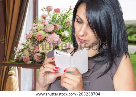 Young beautiful lady using her smartphone  - stock photo