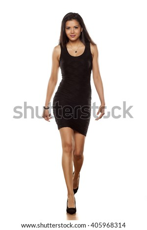young beautiful lady walking in short black tight dress - stock photo