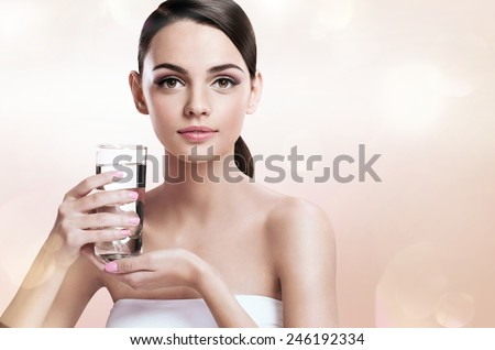 Young beautiful lady with glass of clear water, healthy life concept / photoset of the European appearance girl holding a transparent glass of water - isolated on white background  - stock photo