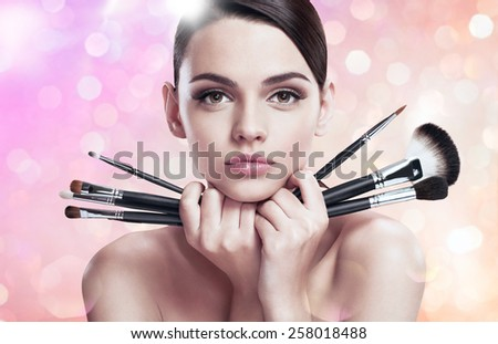Young beautiful lady with makeup brushes near her face, skin care concept / photoset of attractive brunette girl on blurred pink background with bokeh   - stock photo