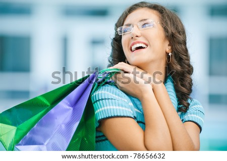 Young beautiful laughing woman in blue sweater with purchases from shop.