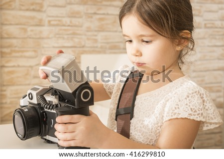 Young beautiful little girl photographer holding old vintage film photo camera. Children's play. Art or creativity concept.  - stock photo