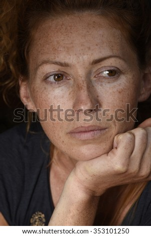 young beautiful lonely freckled woman without makeup brown eyes looking away close up - stock photo