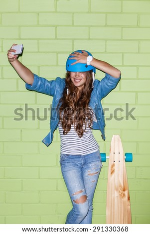 young beautiful long-haired brunette girl in blue helmet with wooden longboard skateboard taking a selfie self portrait of herself coquettishly posing at the camera on her smartphone digital camera  - stock photo