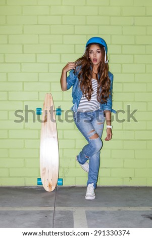 young beautiful long-haired brunette lady in blue helmet with wooden longboard skateboard coquettishly stands near the green brick wall - stock photo