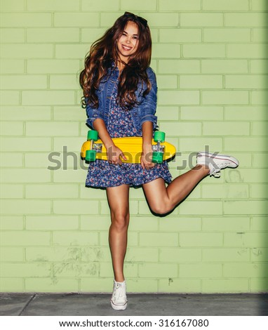 young beautiful long-haired girl with yellow plastic penny board skateboard jumping on one leg against the green brick wall - stock photo