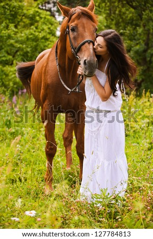 Young beautiful long-haired woman wearing white dress kissing brown graceful horse at summer green park.