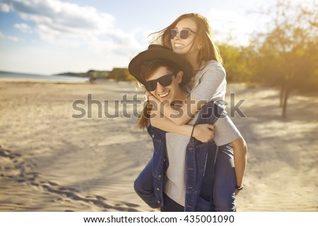 young beautiful loving couple in hipster fashion style posing on a Sunny beach in the shirt t-shirt baseball cap and sunglasses, happily smiling and laughing. outdoor close up portrait  - stock photo