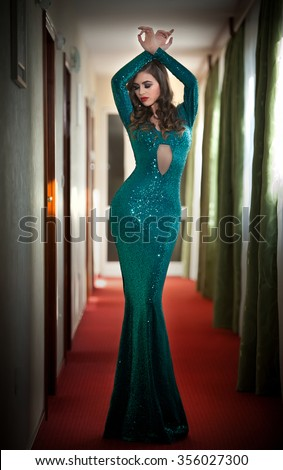 Young beautiful luxurious woman in long elegant turquoise dress posing indoors. Attractive brunette with tight fit glamorous dress in hotel lobby. Fashionable seductive female on red carpet of hall - stock photo