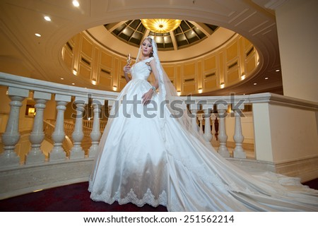 Young beautiful luxurious woman in wedding dress posing in luxurious interior. Bride with huge wedding dress in majestic manor. Seductive blonde bride with gorgeous gown and long dally posing