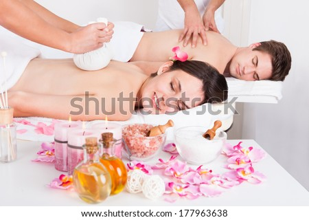 Young Beautiful Man And Woman Getting Massage In Spa - stock photo