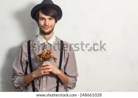 Young beautiful man in hat standing with small dry roses in his hands on white grunge background - stock photo