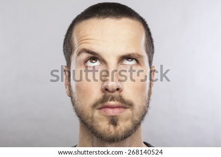 young beautiful man looking up, face expression - stock photo