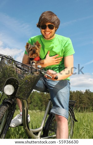 Young beautiful man riding a bike with his small yorkshire terrier
