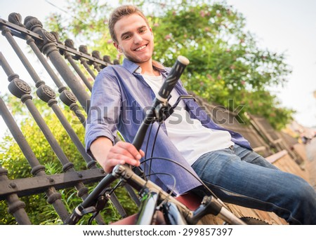 Young beautiful man standing with bicycle at the city street near the fence.