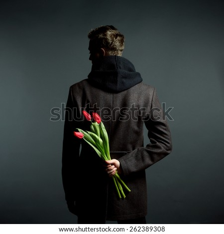 Young beautiful man with flowers