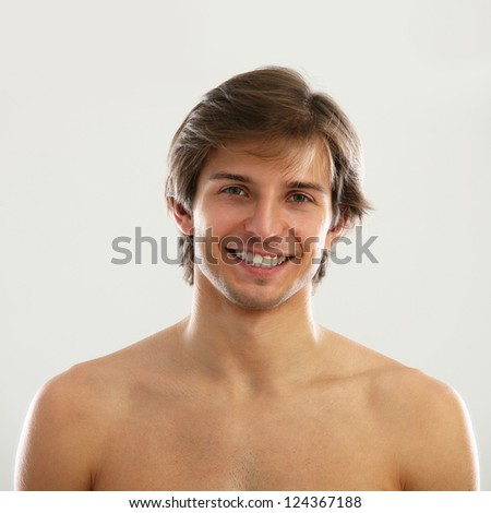 Young beautiful man with naked torso isolated over white background - stock photo