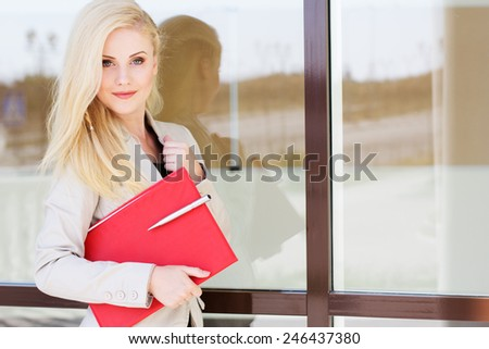Young beautiful manager girl is holding pen and red folder over window - stock photo