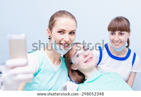 Young beautiful medical doctors dentist hygienist orthodontist and her assistant making selfie on their phone with happy patient smiling after successful treatment - stock photo