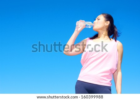 young beautiful mixed race girl drinking bottle of water on a nice spring day. Color image, copy space.