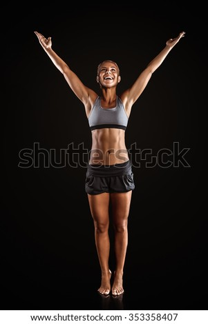 Young beautiful mixed race sportswoman on black background. Fit sporty woman smiling, stretching and throwing up hands
