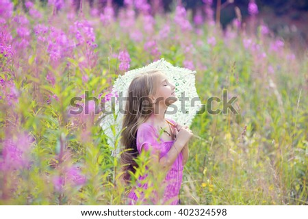 Young beautiful model girl wearing pink dress dream with lace umbrella in blooming flowers field - stock photo