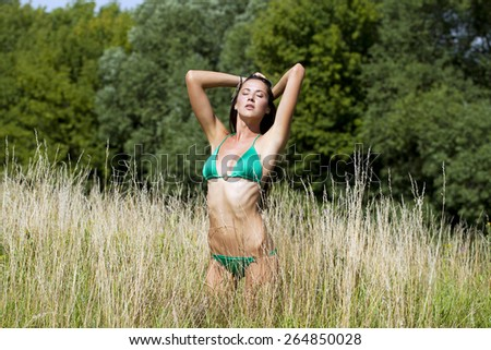 Young beautiful model in a green bathing suit standing in the summer field