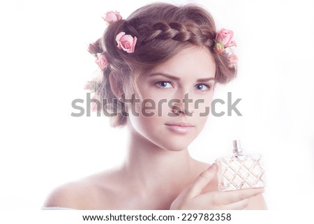 Young beautiful model showing a fragrance bottle - stock photo
