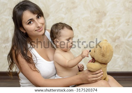 Young beautiful Mom playing with baby toddler at home - stock photo