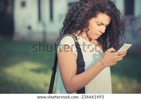 young beautiful moroccan curly woman using smartphone at the park
