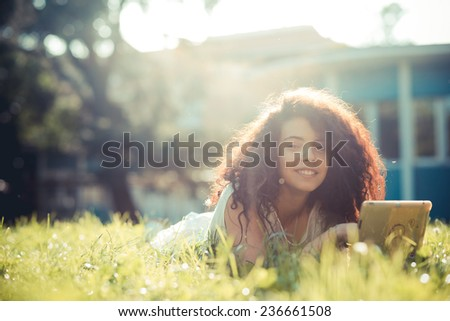 young beautiful moroccan curly woman using tablet at the park - stock photo