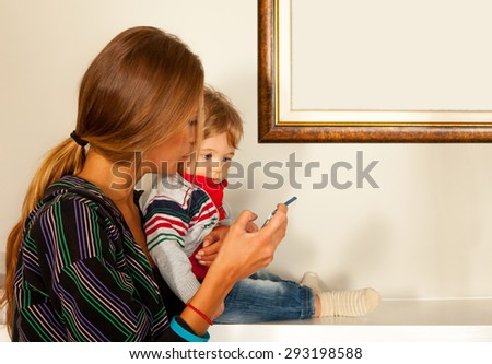 Young beautiful mother and a cute blue eyes child are looking at a smartfone indoors. Copy space frame. - stock photo