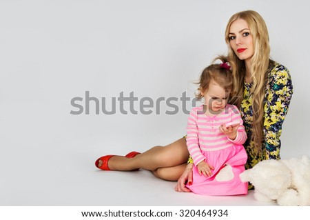 Young beautiful mother and daughter sitting - stock photo