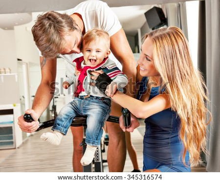 Young beautiful mother and father having fun embracing their cute  little boy with affection in a cycling gym. - stock photo