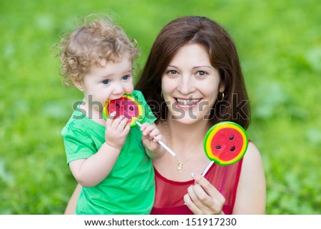 Young beautiful mother and her adorable curly baby daughter eating water melon candy in a summer park - stock photo